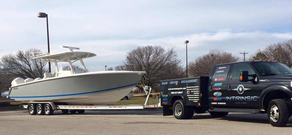 Invincible being towed by truck, spring commissioning